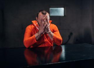 Desperate prisoner sitting alone in interrogation room