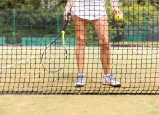 Female tennis player legs on grass court seen through the net