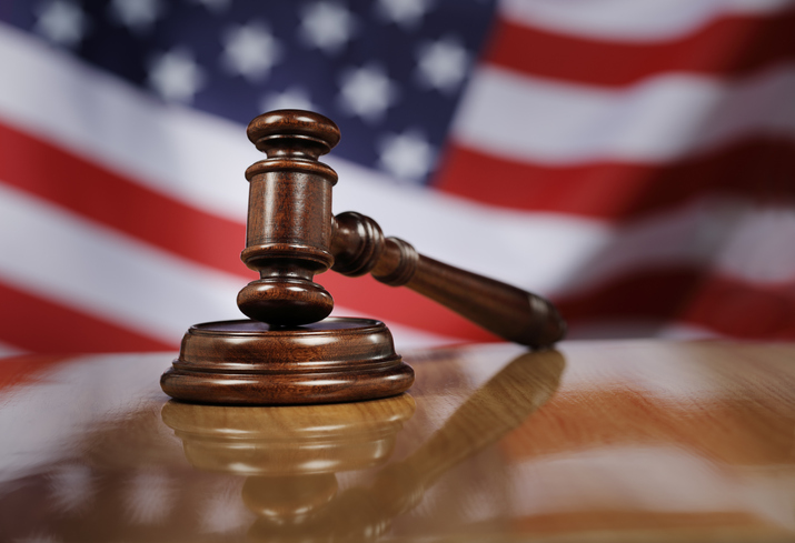 Close-Up Of Gavel On Wooden Table Against American Flag