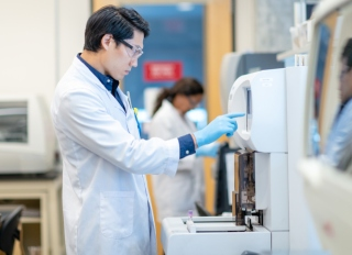 Asian Scientist Setting Medical Testing Equipment stock photo
