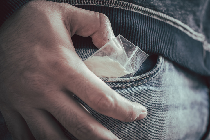 Close-Up Of Man Putting Cocaine Packet In Pocket