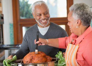 Black couple preparing Thanksgiving turkey - stock photo