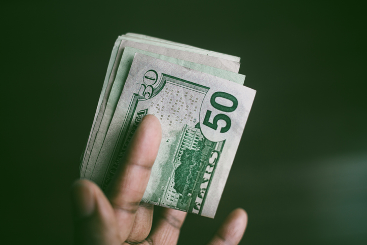 Close-Up of Hand Holding Folded Stack of US Currency