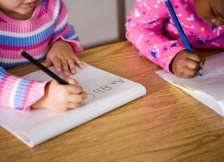 Two girls (5-7) writing at desks in classroom, mid section - stock photo