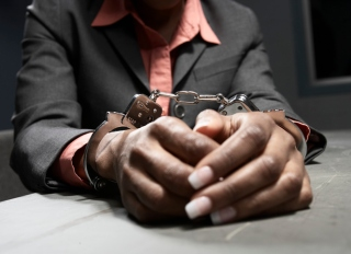 Woman in handcuffs, mid section, close-up of hands
