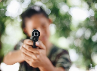 Close-Up Of Handgun Holding By Person Outdoors