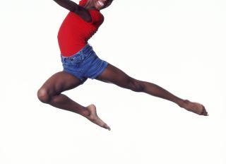 Girl (9-11) dancing in mid leap