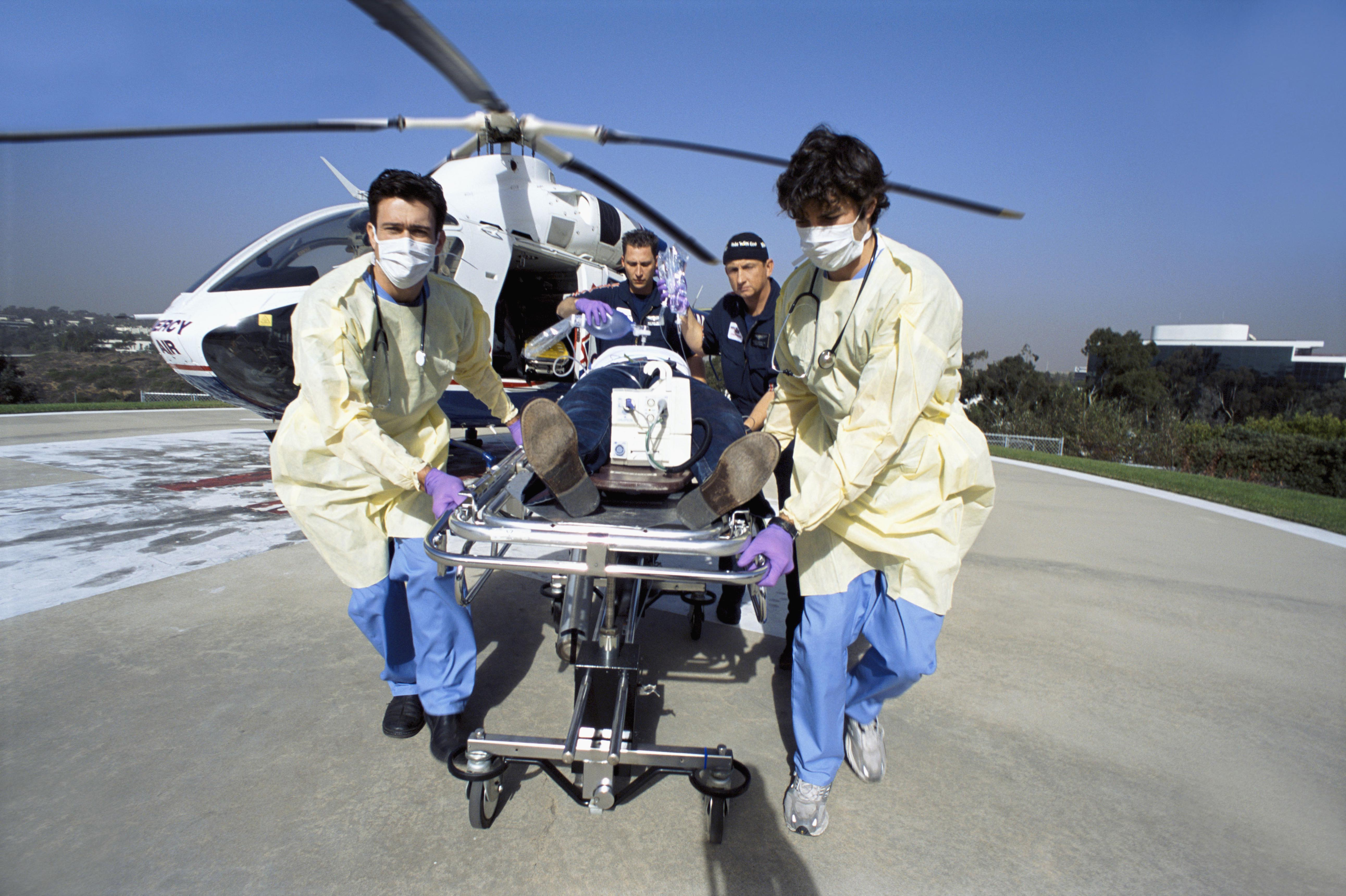 Doctors and paramedics rushing patient on gurney from emergency airlift helicopter