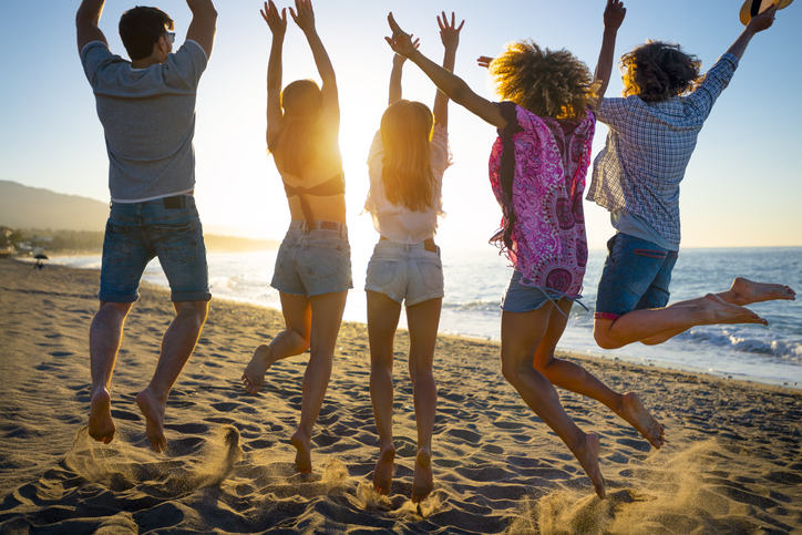 Group of friends jumping for joy on the beach at sunset or sunrise.