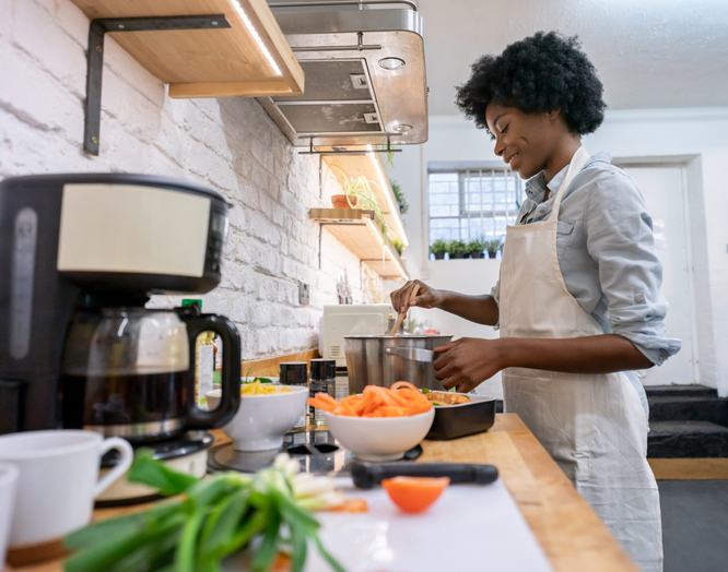 Happy African American woman cooking dinner at home
