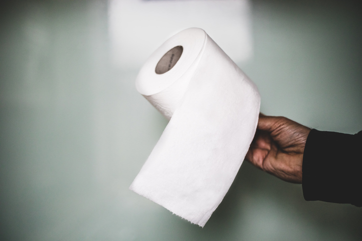 A man holding a roll of toilet paper