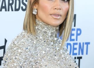 Actress/singer Jennifer Lopez wearing a Valentino top and skirt, Jimmy Choo shoes, a Judith Leiber c...