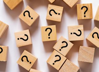 Question Marks on Wooden Block White Background