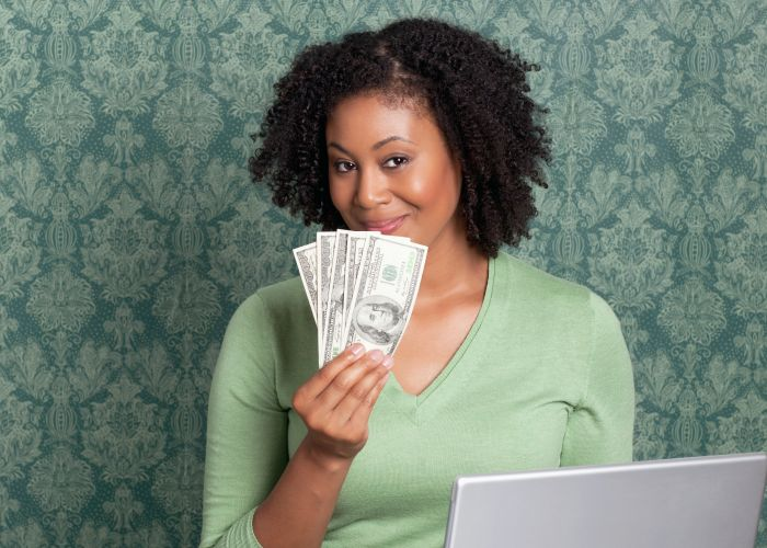Woman holding currency in front of laptop - stock photo