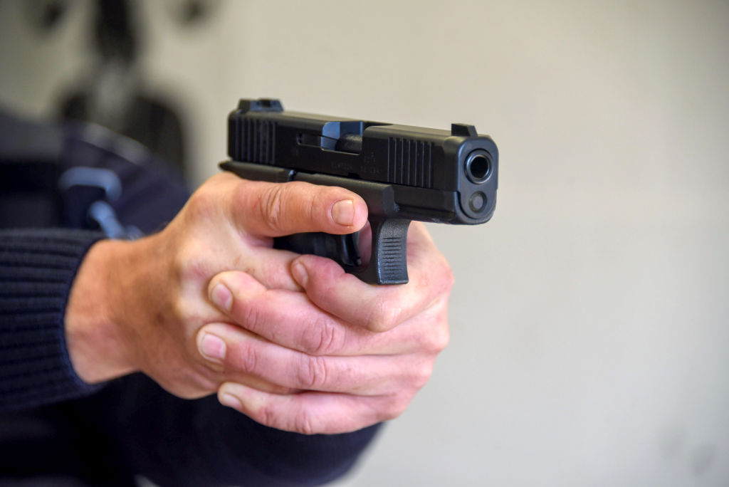 Policeman points a pistol at a shooting range