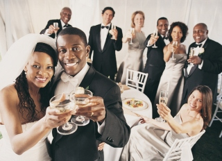 Group of People Toast a Bride and Groom at a Wedding reception in a Marquee
