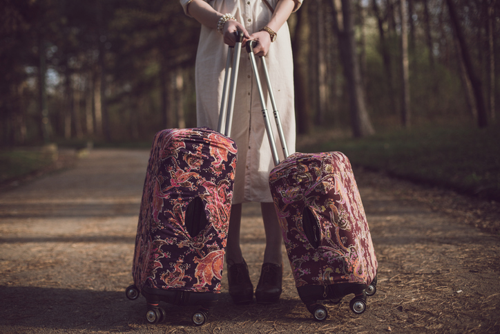 Woman wearing white dress holding suitcases in the park