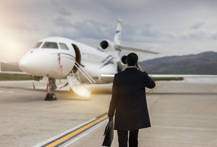 Rear View Of Businessman Walking Towards private airplane