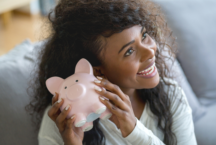 Beautiful black woman holding her pinbk piggy bank trying to guess how much money she has