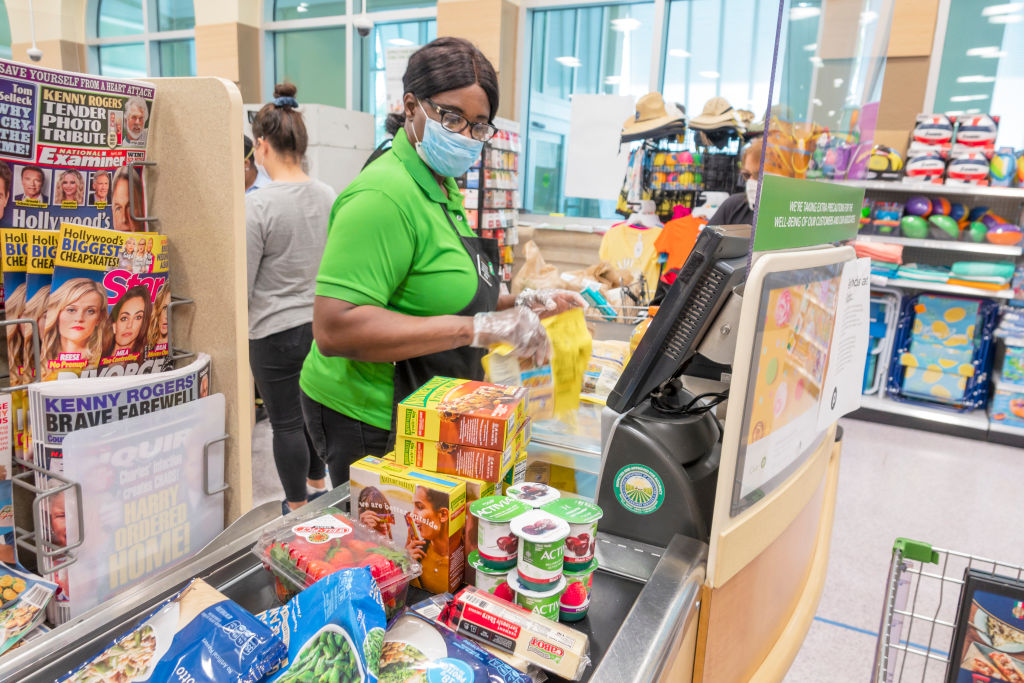 Miami Beach, Publix grocery store, cashier wearing face mask, gloves and new plexiglass shield protection