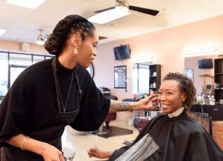 Female hairdresser checking clients hair