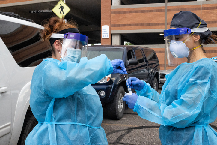 A Female Nurse Wearing a Gown, Surgical Face Mask, Gloves, and a Face Shield Places a Used Cotton Swab into a Test Tube Held by Another Nurse in a Drive-Up COVID-19 Testing Line Outside a Medical Clinic/Hospital Outdoors