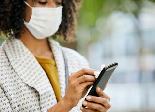 Close-up of Businesswoman Disinfecting Phone With Wet Wipe in city. She is Wearing Protective Face Mask.