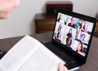 Unrecognizable woman uses video conferencing for book club