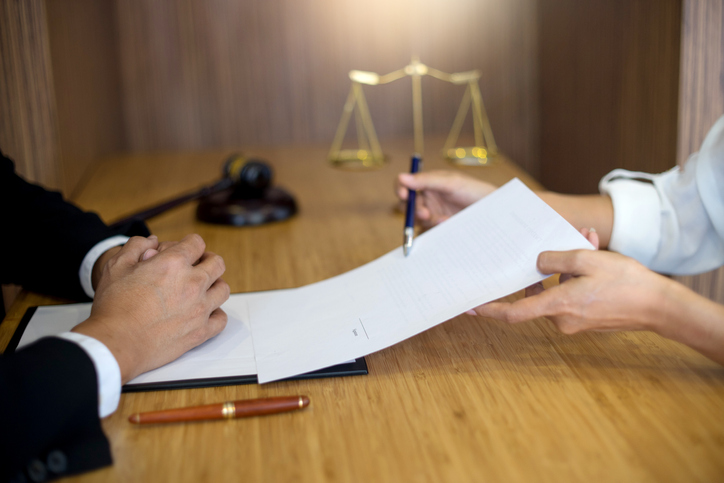 Cropped Hands Of Lawyer Showing Businessman To Sign Paper On Table