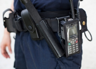 Midsection of a police officer with walkie-talkie and night stick on equipment belt