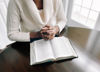 Woman Reads Bible at Kitchen Table