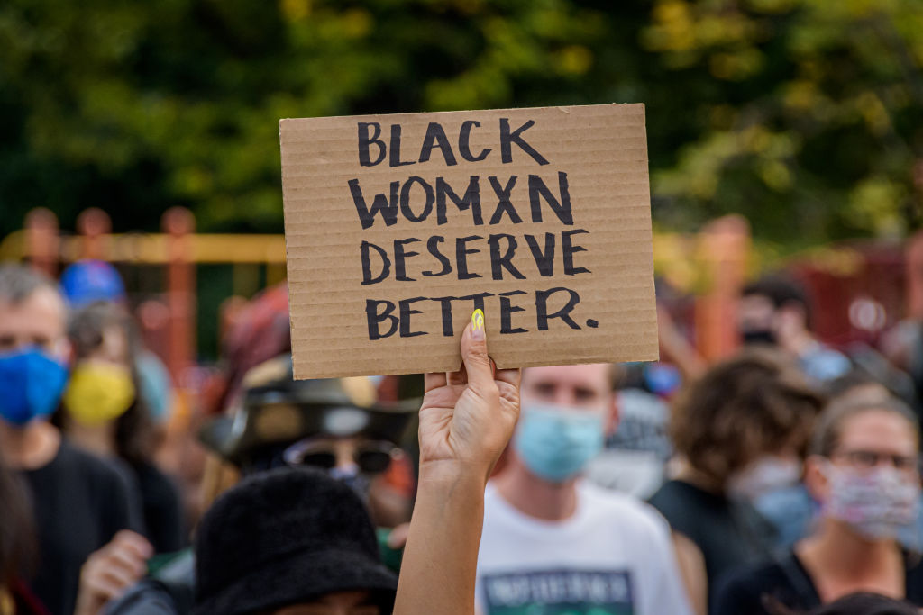 A participant holding a Black Women Deserve Better sign at...