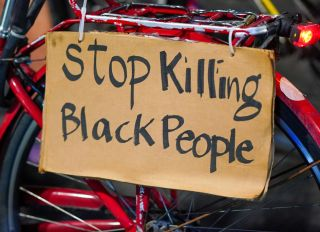 A 'Stop Killing Black People' placard seen on a bike during...