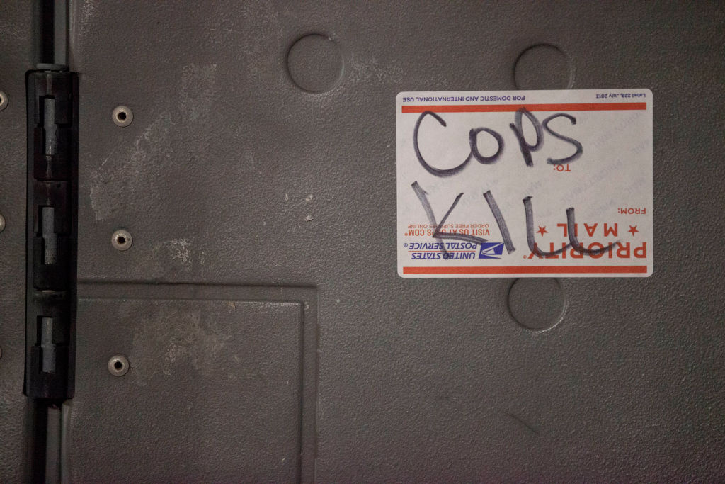 """""""Cops Kill"""" is scrawled on a United States Postal Service..."""
