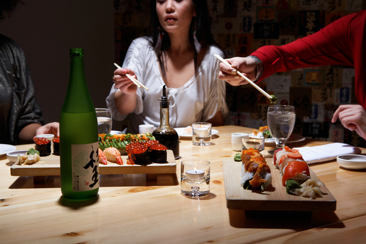 Three young women eating sushi in restaurant, mid section