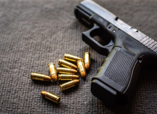 Close-Up Of Gun With Bullets On Table