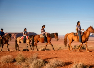 Four Young Native American Navajo Brothers and Sisters Riding their Horses Bareback in the Northern Arizona Monument Valley Tribal Park At Dusk Together