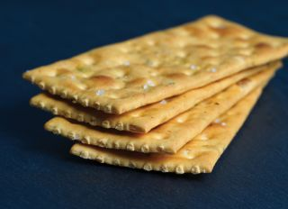Stack of Delicious salty crackers isolated on black background - stock photo