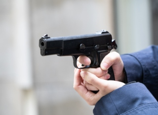Cropped Hand Of Police Holding Handgun Outdoors