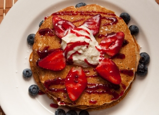 Pancakes with berries. A short stack of pancakes sits on a...