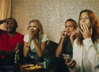 Disappointed heterosexual couples watching sports together at night