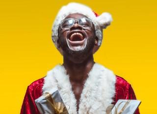 Excited black man in Santa Claus costume - stock photo