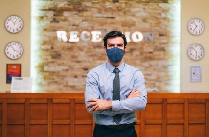 Manager of a luxury hotel wearing protective face mask with arms crossed, during Covid tourism and hotel reopening