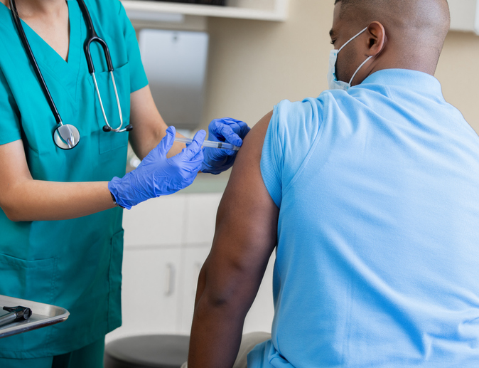 Nurse gives mature African American man a vaccination in doctor's office during coronavirus pandemic