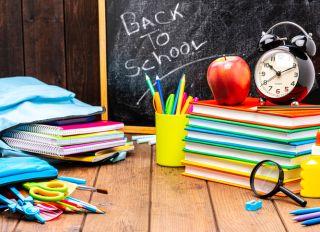 Back to school: multicolored school supplies shot on wooden desk.