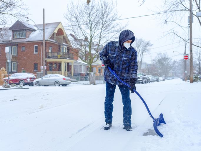 Senior man snow shovelling