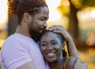 Cheerful African-American Couple is Sharing the Love in Public Park.