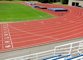 Sweeping Curve of Red Asphalt Running Track Within Stadium