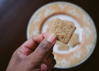 Woman Snacks on Whole Grain Crackers
