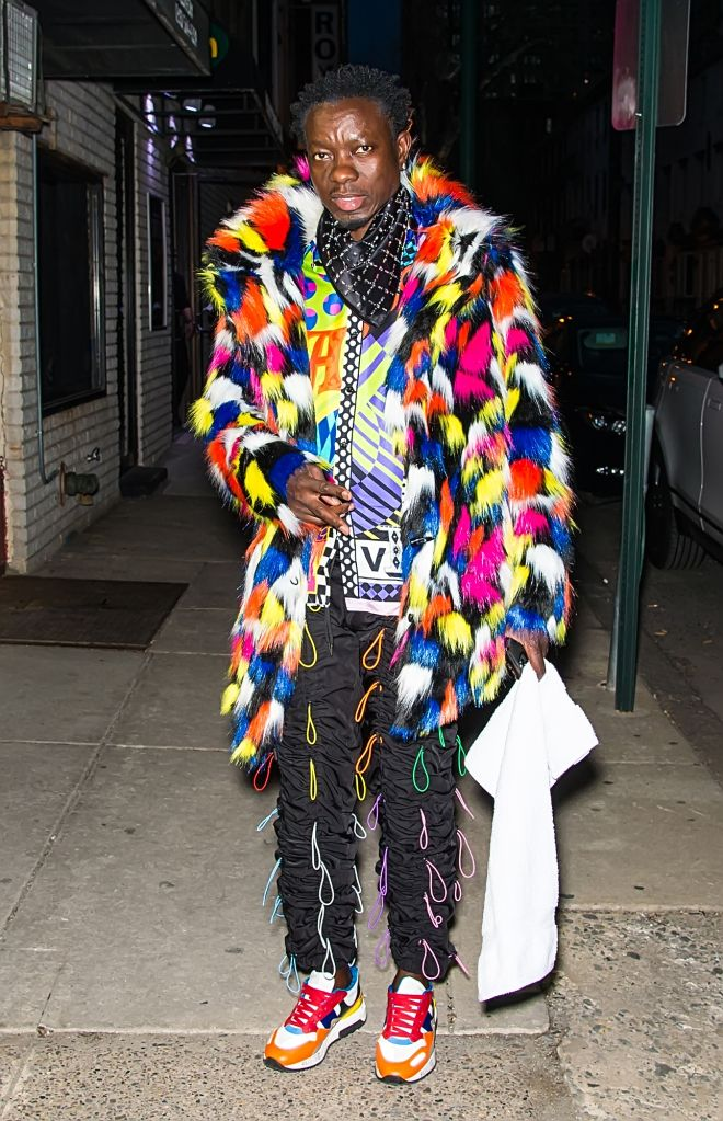 Michael Blackson in hair tie pants and colorful shirt